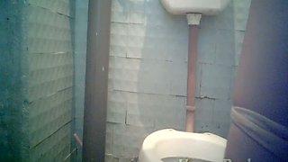 Pale skin brunette lady filmed from front side in the toilet