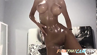 Excessively oiled sexy nude body on webcam display