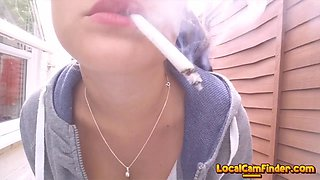 Brunette smoking outdoor and tease