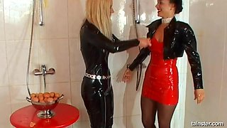 Babes in latex outfits play with each other's bodies in a shower