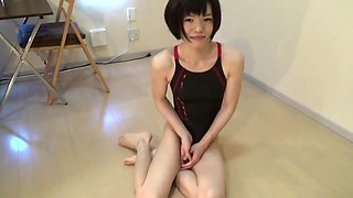 Crossdresser in a black swimsuit sitting and lying