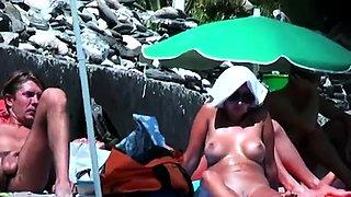 Beach voyeur finds a busty milf under the hot sun